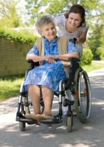 Eldery-mother-with-grown-daughter-pushing-wheelchair