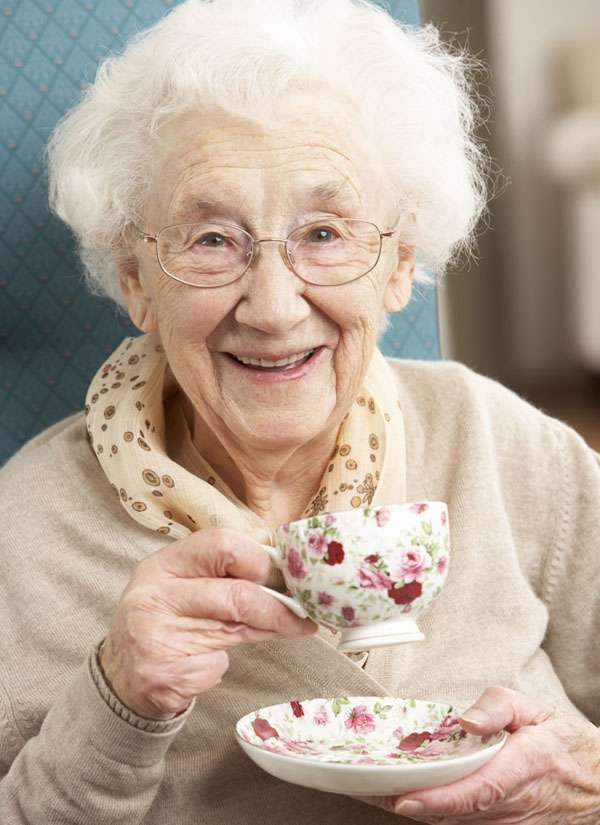 Smiling client holding a cup of tea