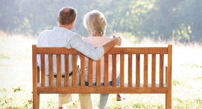 man and woman sitting on a bench outside